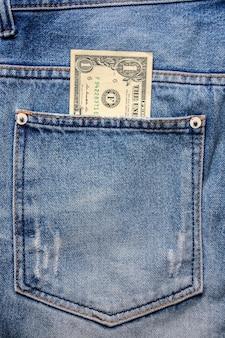 Деньги в заднем кармане джинсовой ткани синих джинсов.