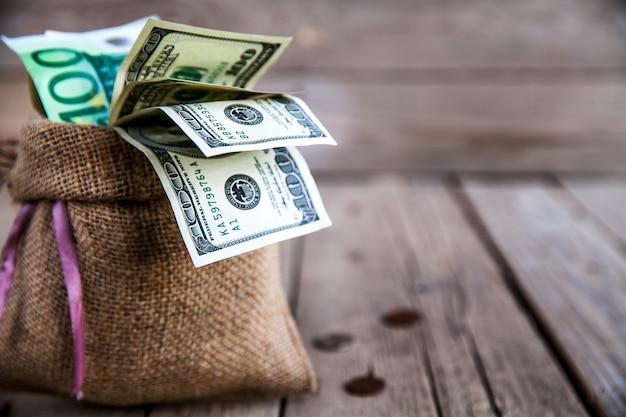 Деньги в мешковине с разбросанными деньгами на деревянном фоне