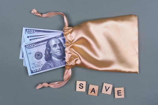 Деньги в золотой подарочной сумке с надписью save.