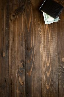 Деньги в кожаном кошельке на деревянных фоне