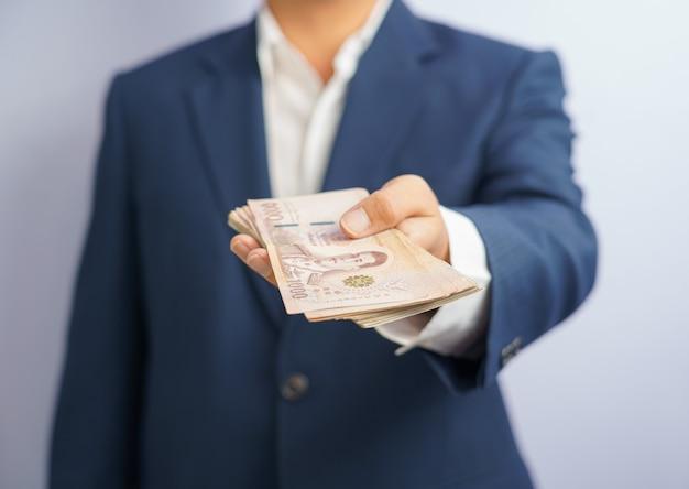 タイのお金は青いスーツを着てつかむビジネスマンを手に持っています
