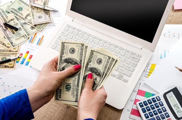 노트북과 그래픽의 손에있는 돈