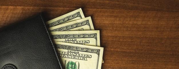 Деньги в кошельке, сто американских банкнот в черном мужском кошельке, фон деревянный стол, вид сверху и копия космического фото