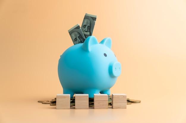 Деньги в копилку, изолированные на оранжевом фоне, рассчитывают доходы и расходы в повседневной жизни.