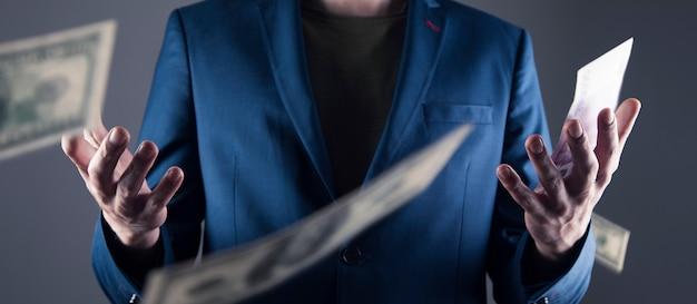 회색 벽에 양복 입은 남자에게 돈이 떨어지고있다.