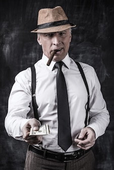 Money is not a problem. serious senior man in hat and suspenders smoking cigar and stretching out money while standing against dark background