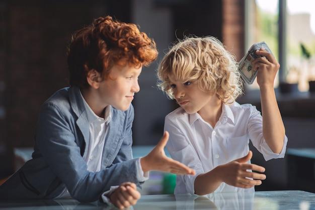 Проблемы с деньгами. рыжий мальчик просит денег у друга