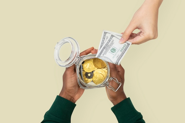 手で保持するお金の瓶は、貯蓄の概念を融資します