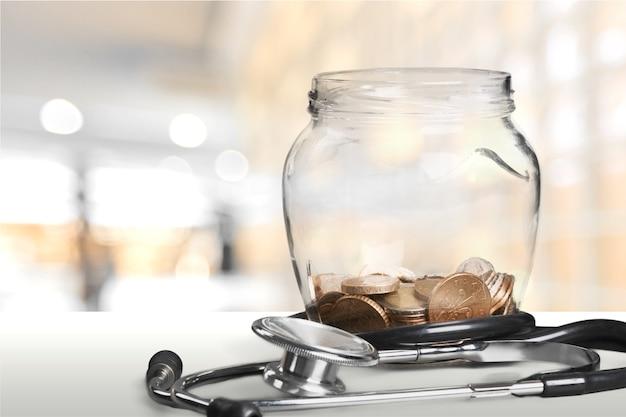 Денежная банка с монетами и стетоскопом