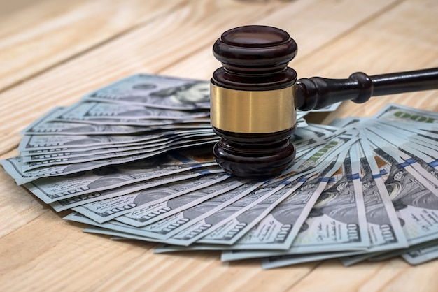Money and judges hammer on wooden table