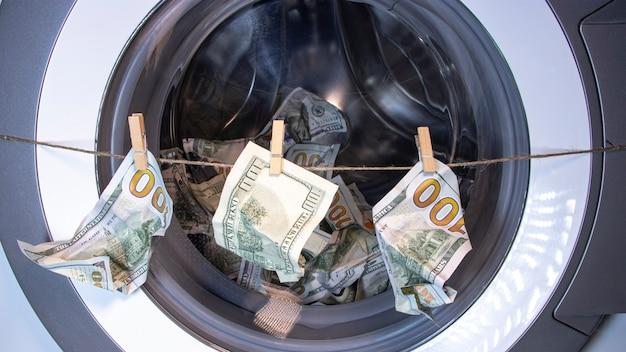 돈 세탁. 세금의 부패 은폐. 세탁기 드럼에 있는 달러. 소셜 광고에 대한 개념입니다.