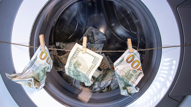 Money laundering. corruption concealment of taxes. dollars in the drum of a washing machine. concept for social advertising.