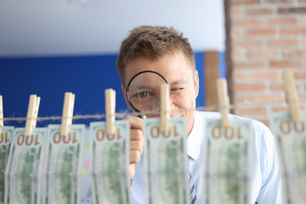 Money laundering. man looks through magnifying glass at one hundred dollar bills hanging on clothespins.