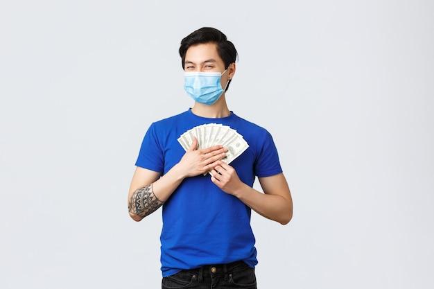 돈, 라이프 스타일, 보험 및 투자 개념입니다. 만족스러운 아시아 남성이 현금을 껴안고 의료용 마스크를 쓰고 복권을 받거나 당첨되었습니다.