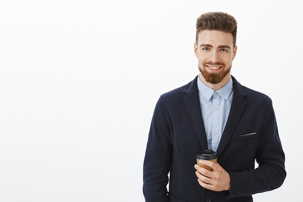 Деньги любят уверенность. уверенный в себе харизматичный и умный красавец с каштановыми волосами, бородой и голубыми глазами держит бумажный стаканчик кофе, счастливо улыбаясь, встречая симпатичную девушку после работы в кафе