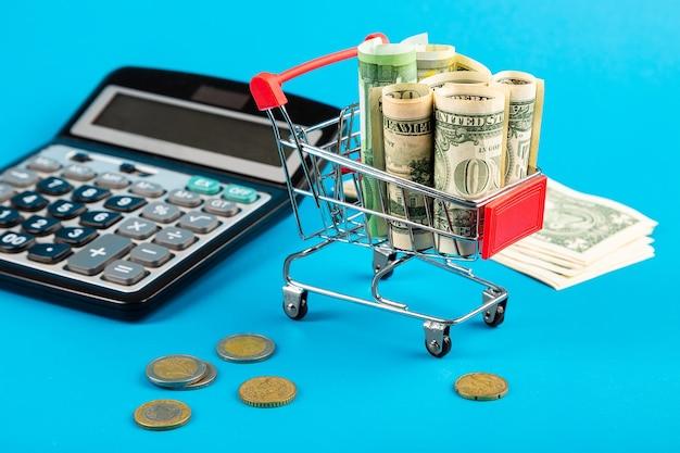 お金は請求書が大好きです。ユーロ、ドル、電卓付きの買い物かご。閉じる。