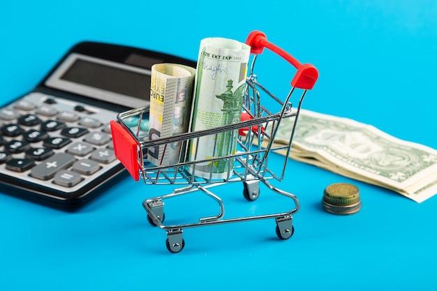 Деньги любят счет. корзина для покупок с евро, долларом и калькулятором. крупный план.