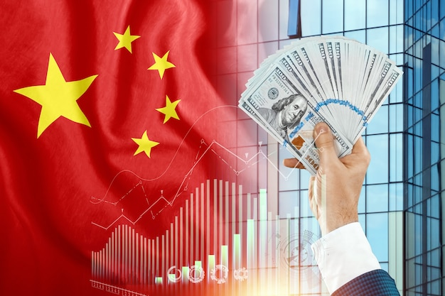 Money in a man's hand against the background of the flag of china