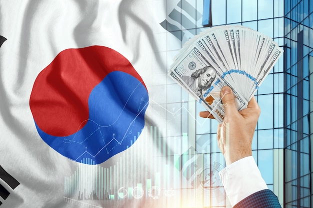 Money in a man's hand against the background of the flag of south korea