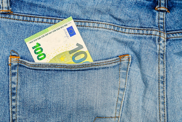 Money in my jeans pocket, one hundred euros in the back pocket of blue jeans. wealth and prosperity concept. place for text. copy space.