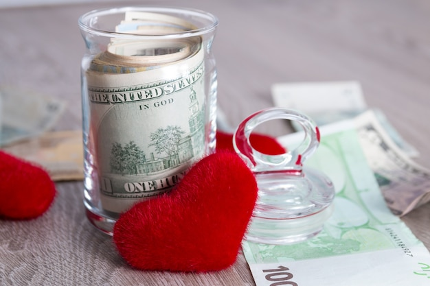Money near red hearts dollars in open jar with euro on grey wooden surface
