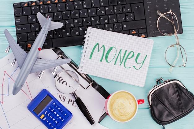 여행용 액세서리 안경 지갑과 비행기가 나무 탁자 위에 있는 노트북에 돈. 여행 비용의 개념입니다.