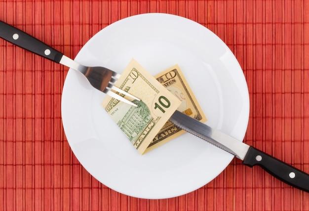 Деньги на тарелке с вилкой и ножом. бизнес и финансовая концепция.