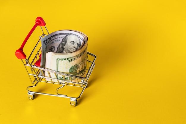 黄色の背景のカートのチューブにお金やドルが転がり込んだ。販売とショッピングのコンセプト。無料の広告スペース