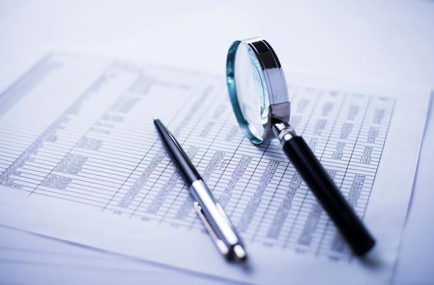 돈, 펜, 돋보기 및 재무 보고서