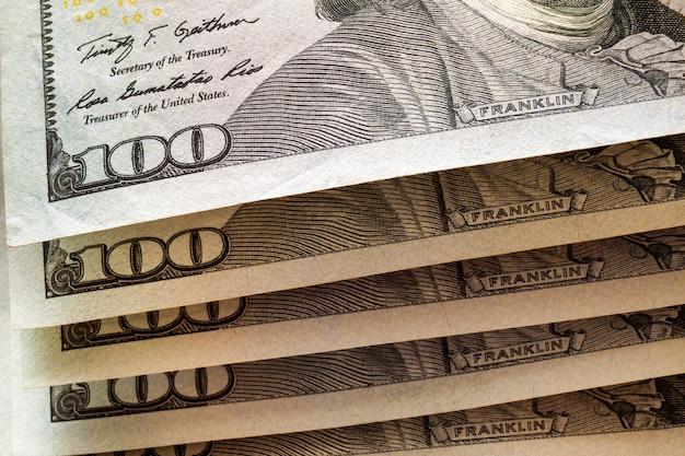 お金、繁栄、財政の概念。アメリカのアメリカの国の通貨紙幣、100ドルの価値があるきちんと積み重ねられた手形の詳細の抽象的な光。