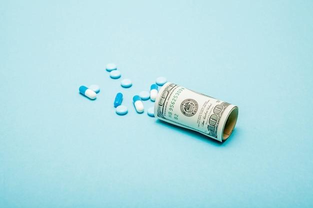 Деньги, свернутые с таблетками, вытекающими изолированными на синем фоне, высокие затраты на концепцию дорогих лекарств. скопируйте пространство.