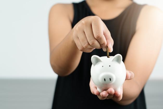 お金の節約と寄付のコンセプト、子供はかわいい白い貯金箱にお金を置く