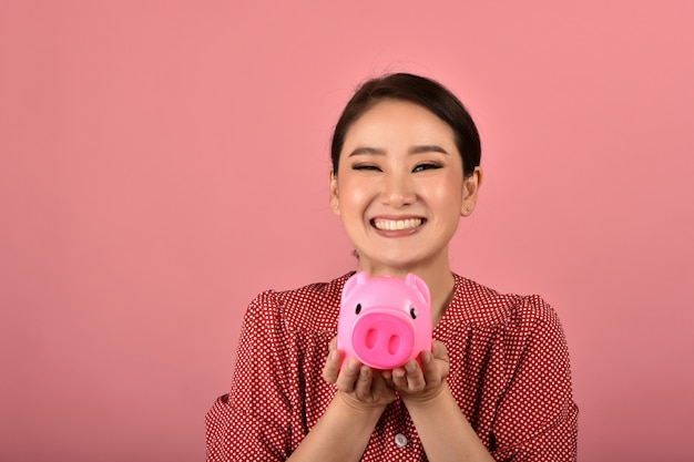 Money saving, asian woman smiling and holding pink piggy bank, wealth and financial planning insurance for investment.