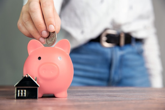 Money saving for buying a new house in pink piggy bank , real estate,mortgage,loans,business concept with space for text copy space on wooden table