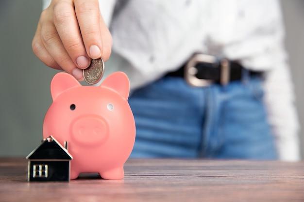 핑크 돼지 저금통, 부동산, 모기지, 대출, 나무 테이블에 텍스트 복사 공간에 대 한 공간을 가진 비즈니스 개념에 새 집을 구입을위한 돈 절약