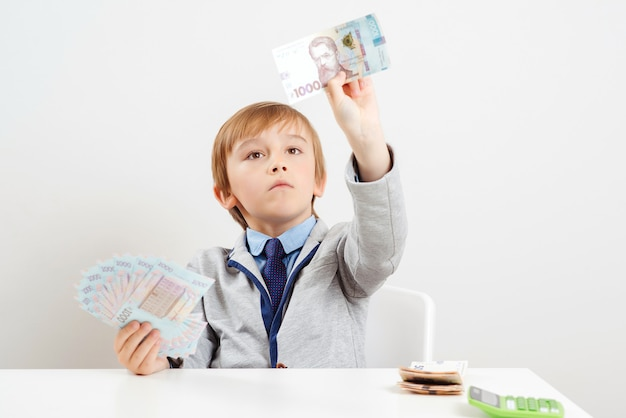 Money and savings concept. boy with calculator acounts money.