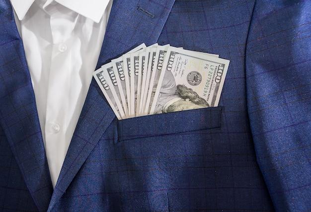 お金の成功の概念。ビジネスマンのジャケットのポケットに100ドル札。成功と富の象徴。