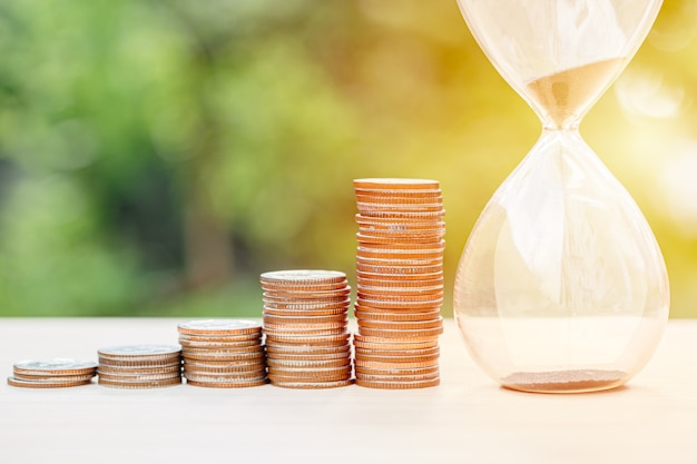 Money times memory concept, coins stack with sand hourglass