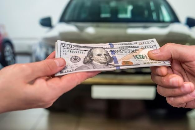 新しい車を買うお金。財務コンセプト。手にドル