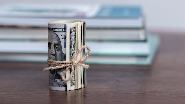 Деньги (доллары сша) в рулоне, перевязанном веревкой, возле стопки книг