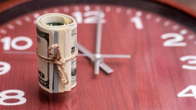 時計のロープで結ばれたロールのお金(米ドル)