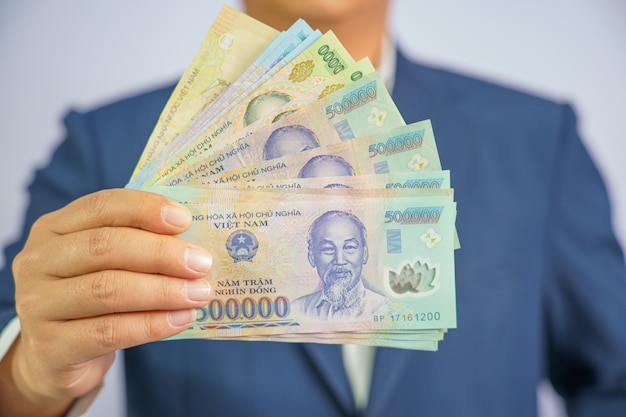 Money in vietnam hold on hand business man wearing a blue suit