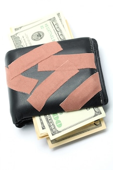 Money in wallet with medical plaster