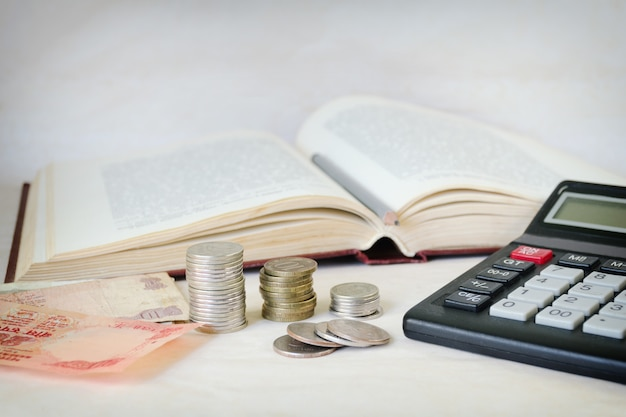 Money with calculator in front of an open book.
