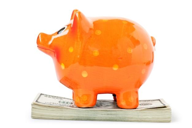 白い背景で隔離の貯金箱とお金