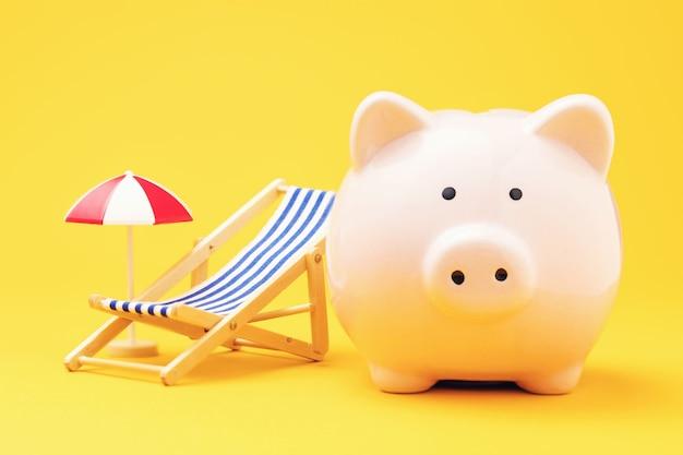 休息のためにお金を節約するという黄色の背景のコンセプトの貯金箱とビーチアクセサリー