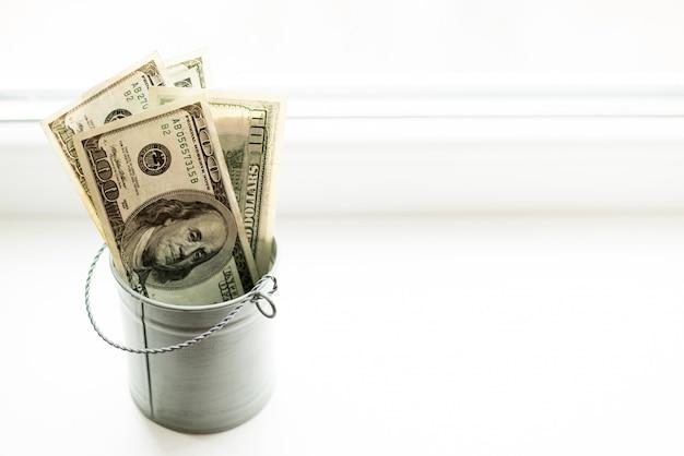 Moneybox, dollars in bucket on white window.light background