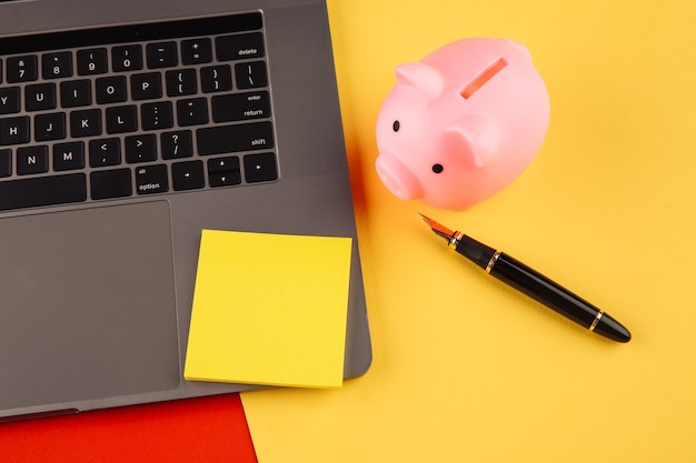 Moneybox near laptop and yellow sticky note, place for text. finance and budget concept. piggy bank in pink color with gadgets and stationery on colorful background.