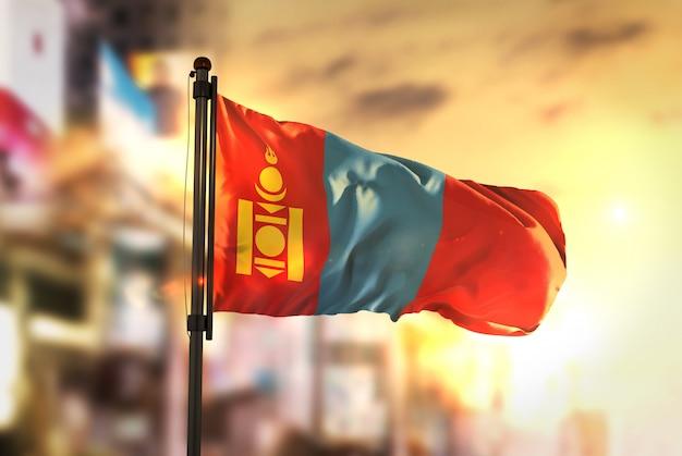 Mongolia flag against city blurred background at sunrise backlight
