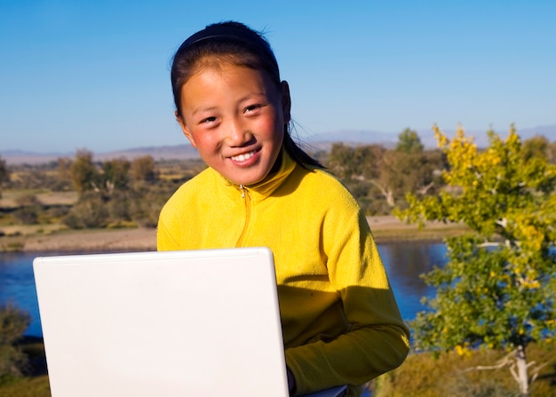 Mongolian girl with laptop by lake.